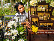 26 DECEMBER 2014 - MAE KHAO, PHUKET, THAILAND: A woman places a flower on a Buddhist alter at a memorial service in Mae Khao, Phuket, for people killed in the 2004 tsunami. Mae Khao was used as a the main morgue for people killed in the tsunami. Nearly 5400 people died on Thailand's Andaman during the 2004 Indian Ocean Tsunami that was spawned by an undersea earthquake off the Indonesian coast on Dec 26, 2004. In Thailand, many of the dead were tourists from Europe. More than 250,000 people were killed throughout the region, from Thailand to Kenya. There are memorial services across the Thai Andaman coast this weekend.    PHOTO BY JACK KURTZ