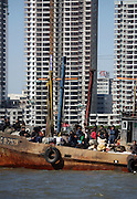 North Koreans use old fishing boat as a ferries on the Yalu River with the Chinese town of Dandong in the background. DPRK, north korea, china, dandong, border, liaoning, democratic, people's, rebiblic, of, korea, nuclear, test, rice, japan, arms, race, weapons, stalinist, communist, kin jong il