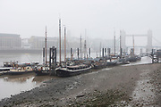 Misty morning in Wapping looking over Hermitage Wharf across the River Thames towards Tower Bridge in London, United Kingdom.