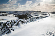 A snow covered scene from near Hucklow Edge. Looking towards Bretton Clough and Sir William Hill. Peak District National Park, Derbyshire, England, UK