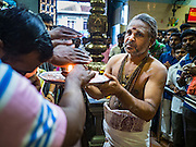 "27 DECEMBER 2015 - SINGAPORE, SINGAPORE:  A Hindu priest participates in services at Sri Veeramakaliamman Temple in Singapore. Sri Veeramakaliamman Temple in the ""Little India"" section of Singapore, was one of the first Hindu temples in Singapore and is dedicated to the Goddess Kali, the Hindu ""Destroyer of Evil.""  It's on Serangoon Road, which at one time was the center of Singapore's Indian community and served Indian immigrants who worked in the cattle trade that was based around Serangoon Road in the 19th century. Now the temple is a popular tourist site.     PHOTO BY JACK KURTZ"