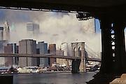 September 11 2001 World Trade Center first tower collapsing. Manhattan Bridge pillar in the foreground.