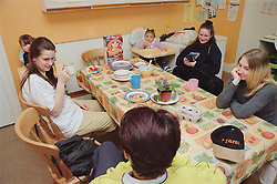 Weekly group meeting of residents in communal kitchen of women only homeless hostel,