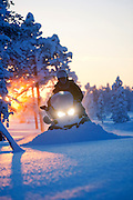 A snowmobile powers through deep snow in the forest near Kirkeness, Finnmark region, northern Norway