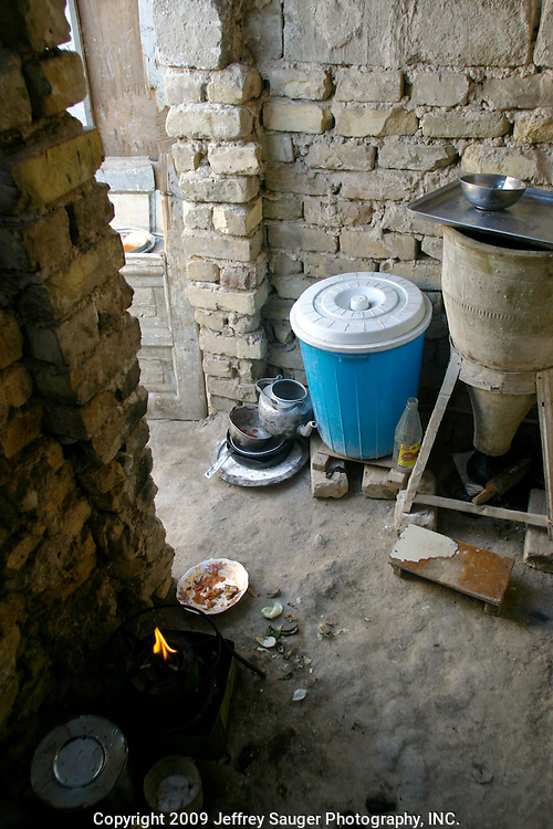 The kitchen area in Hassan Atshan Nassar's one-room home attached to the back of an elementary school in the modernized center of the village Suq ash Shuyukh on the outskirts of Nasiriyah, Iraq, Sunday, August 3, 2003. To support his family of seven, he is a security guard at the school and earns $60 USD/month. Before Saddam Hussein was toppled, he earned about $10/month...Since the 1991 uprising against Saddam Hussein in Shiite dominated Southern Iraq, people of this area have suffered greatly through his methods of disrupting daily life. For example, modernization came to a hault as money was diverted to Baath Party strongholds. Check points on on every other corner made it nearly impossible to go to work, the doctor, or visit family. Teachers made $5 U.S. per month and had to spend almost all of their salary for taxis in order to go to work...He tried to kill the people by cutting off the rivers that village survival depends on. Dams and canals dirverted the fresh water from flowing into the swamps by way of tributaries. In effect, without fresh water flowing in, the people started poisoning the water supply themselves by using it to wash and clean. Their primitive sewers still flow freely into the same waters that animals use and that feed their rice fields.