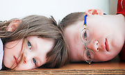 young girl of four and brother of six lying head to head facing camera model release available
