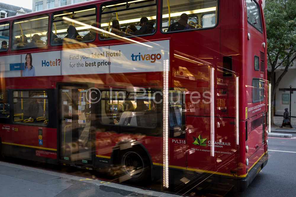 Vertical lighting from Pret a Manger chilled food cabinets and a London bus parked at a bus stop, on 17th October 2017, in the City of London, England.