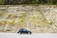 A road cut above a highway in Montana with a car driving by.