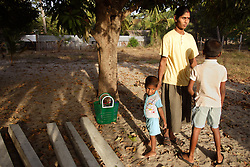 Wassanthy Partheepan and sons, left to right, Vithusan and Sivaskaran, stand under a tree on their new land, Batticaloa, Sri Lanka, July 9, 2005. The family, who lost a 4 year old girl named Madusia, first took refuge in the Anapandi Hindu temple after their house was flattened in the tsunami. They were then moved to the Hindu college and placed in tents donated by aid organizations. Six months later, they were still living on the land where their tents were set up, but they also had a partition of their own in a tin hut with a thatched roof. With earned and borrowed money, plus a little given to them for the loss of Madusia, the family bought a small piece of land, where they plan to start anew.