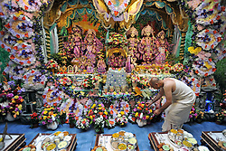 WATFORD HERTFORDSHIRE: A Pujari tends to some of the 4,000 flowers at the Altar. Over 55,000 pilgrims and guests are fed for free as they visit the Largest Hindu Festival in Europe at Bhaktivedanta Manor Krishna Temple near Watford on Sunday 5th September to celebrate Janmashtami the birth of Lord Krishna. The Manor was donated to the Hare Krishna Movement in the early 1970s by former Beatle George Harrison. 03 SEPT 2010. STEPHEN SIMPSON ..