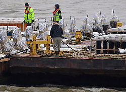 © Licensed to London News Pictures. 31/12/2016. London, UK. Fireworks being installed on a barge on the River Thames ahead of tonight's New Year celebrations. Security surrounding this year's event has been heightened following a terrorist attack at a Christmas market in Berlin earlier this month. Photo credit: Ben Cawthra/LNP