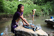 Griselda Peck, 9, does laundry duties at the local river while her younger brother Arden, 5, drinks the river's water. Griselda and Arden are the youngest children of Justino and Christina Peck. Justino, Mopan Mayan cacao grower from San Jose, Toledo, served as TCGA chairman from 1992 to 1997, once again from 2003 to 2010, and is currently the TCGA's liaison officer. Toledo Cacao Growers' Association (TCGA), San Jose, Toledo, Belize. January 25, 2013.