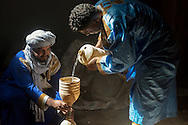A rural scene inside a Kasbah. Two traditional dressed Moroccan men pour water into a canister.
