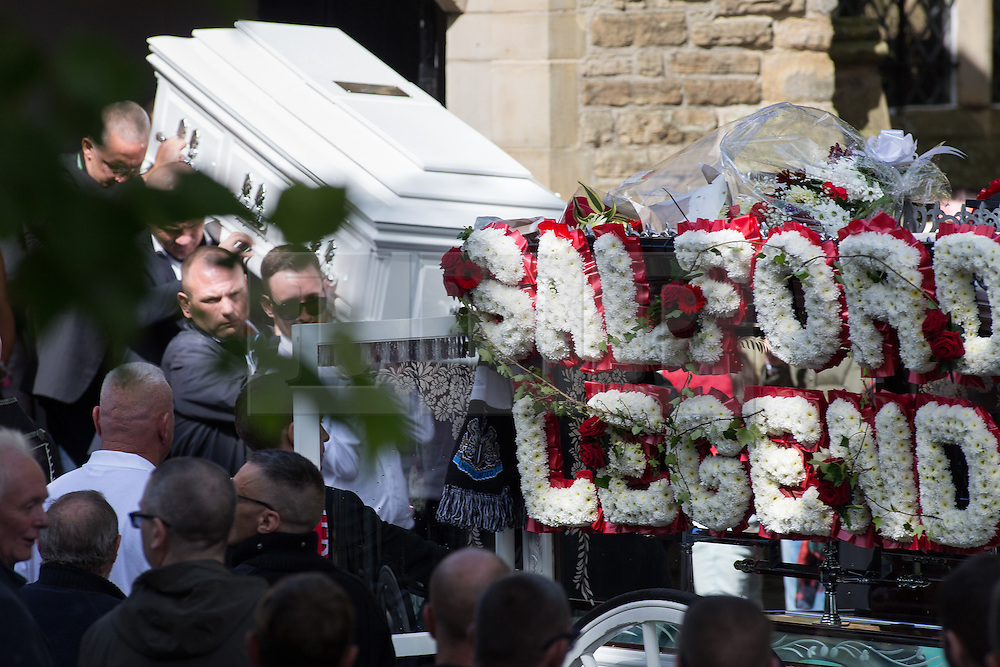 """© Licensed to London News Pictures . 28/08/2015 . Salford , UK . Paul Massey's coffin is carried from the church after the service . The funeral of Paul Massey at St Paul's CE Church in Salford . Massey , known as Salford's """" Mr Big """" , was shot dead at his home in Salford last month . Photo credit : Joel Goodman/LNP"""