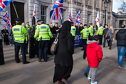 """London, February 8th 2015. Muslims demonstrate outside Downing Street  """"to denounce the uncivilised expressionists reprinting of the cartoon image of the Holy Prophet Muhammad"""". PICTURED: A Muslim woman and her children walk past the far right's counter-protest."""