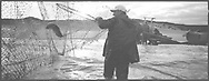 A salmon netter emptying a 'jumper' net at low tide on the sands at Kinnaber, Angus.<br /> Ref. Catching the Tide 49/00/17 (1st August 2000)<br /> <br /> The once-thriving Scottish salmon netting industry fell into decline in the 1970s and 1980s when the numbers of fish caught reduced due to environmental and economic reasons. In 2016, a three-year ban was imposed by the Scottish Government on the advice of scientists to try to boost dwindling stocks which anglers and conservationists blamed on netsmen.