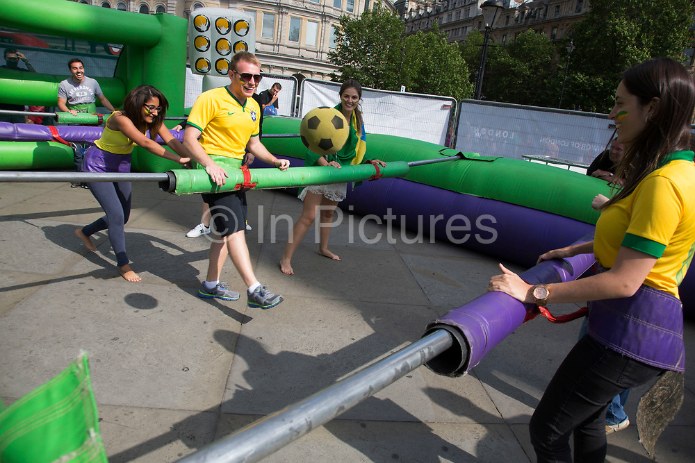 London, UK. Thursday 12th June 2014. Playing human sized table football. Brazilians gather for the Brazil Day celebrations in Trafalgar Sq. A gathering to celebrate the beginning of the Brazil 2014 FIFA World Cup. Revellers sing and dance and play football games and all in the yellow green and blue of the Brazilian flag.