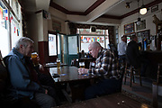 Men drinking in the Cock Tavern in Somers Town on 1st July 2016 in London, United Kingdom. Somers Town, a district in north west London, is a large housing estate nestled between Euston, St Pancras and Kings Cross Library. Predominantly filled with social housing for the past 200 years, much of the area's housing was built in the twentieth century by the local authority.