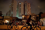 Young men biys ride bikes across the Favela with the city in the background. Favela do Moinho, the last one in the centre of Sao Paulo, hosts its own World Cup opening game and hip hop music event in the central yard of the community, good vibes, Sao Paulo, Brazil. World Cup 2014.