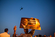 An anti-Morsi demonstrator holds a poster with a statement about US President Obama on a bridge leading to Tahrir Square, Cairo, whilst a military helicopter flys overhead.