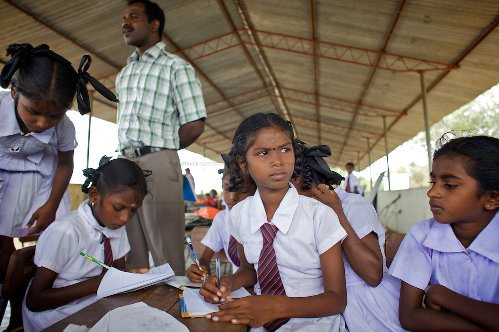 M. Dhanushika, age 11 (looking up) in class in a UNICEF-supplied Temporary Learning Space.<br /> <br /> Sisters M. Dhanushika, age 11 (left) and M. Dilushana, age 9 are from Sri Lanka's Tamil community. They lost their mother in 2006 after she was raped and killed, allegedly by TMVP troops loyal to Colonel Karuna. Their father has subsequently remarried and refuses to be involved in the upbringing of his daughters who live together in a temporary makeshift shelter supplied by UNHCR. The two sisters rely on their aunt and uncle for care. Dhanushika and Dilushana attend Vadamunai Government Tamil Mixed School but often miss classes because they must work collecting reeds which provides them their only source of income. Despite the challenges of their situation, Dhanushika is a particularly conscientious child. As well as taking responsibility for her own necessities, she is committed to her sister's well being. The girls rely on a meal provided by the school every day. Despite the support of neighbours, their present situation is not sustainable and they are likely to be admitted to the care of an orphanage in the near future. <br /> <br /> When fighting between the LTTE and Colombo Government forced the displacement of the local Tamil community in 2007, the Vadamunai Government Tamil Mixed School in Batticaloa District was closed. Since reopening in January 2009, the school has six teaching staff for 88 pupils from Grades 1-9. Before closure,136 pupils studied at the school. Poor road-infrastructure and the remote location of the school means that many staff have to commute for more than three hours. Five classes are held in a UNICEF-supplied Temporary Learning Space. Four other classes are conducted outside, beneath trees. Many of the students suffer with the trauma and stress associated with those living in conflict situations. The staff must deal with these issues as well as the personal difficulties that they themselves suffer living in a conflict environment. To