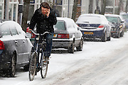 Druk bellend fietst een man in de sneeuw over de Adelaarstraat in Utrecht.<br /> <br /> While on the phone, a man is cycling in the snow at the Adelaarstraat Utrecht.
