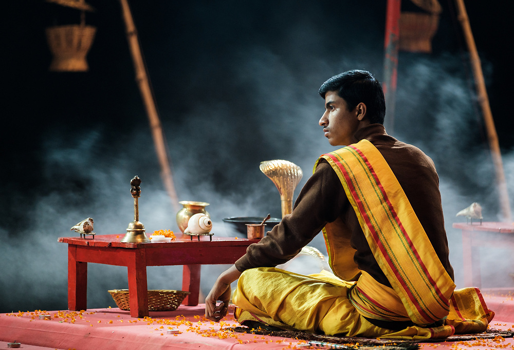 Varanasi, INDIA - CIRCA NOVEMBER 2018: Young priest performing the Ganga Aarti ceremony at the  Assi Ghat in Varanasi. The Aarti is a powerful and uplifting spiritual ritual that takes place every evening at dusk. Varanasi is the spiritual capital of India, the holiest of the seven sacred cities and with that many rituals and offerings are performed daily by priests and hindus.