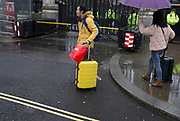 Carrying suitcases, foreign visitors to the capital, makes their way past police officers and the security barrier at the entrance of the British parliament, in Parliament Square, Westminster, on 30th January 2020, in London, England.