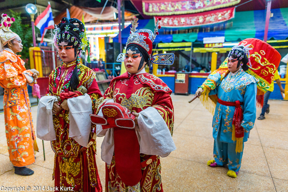 """19 AUGUST 2014 - BANGKOK, THAILAND:  Members of the Lehigh Leng Kaitoung Opera troupe pray in the shrine at the beginning of a performance at Chaomae Thapthim Shrine, a small Chinese shrine in a working class neighborhood of Bangkok. The performance was for Ghost Month. Chinese opera was once very popular in Thailand, where it is called """"Ngiew."""" It is usually performed in the Teochew language. Millions of Chinese emigrated to Thailand (then Siam) in the 18th and 19th centuries and brought their culture with them. Recently the popularity of ngiew has faded as people turn to performances of opera on DVD or movies. There are still as many 30 Chinese opera troupes left in Bangkok and its environs. They are especially busy during Chinese New Year and Chinese holiday when they travel from Chinese temple to Chinese temple performing on stages they put up in streets near the temple, sometimes sleeping on hammocks they sling under their stage. Most of the Chinese operas from Bangkok travel to Malaysia for Ghost Month, leaving just a few to perform in Bangkok.             PHOTO BY JACK KURTZ"""