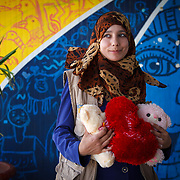 Haneen, 20, and her husband arrived in Azraq last December from Syria. She brought with her wedding gifts from her husband and a teddy bear from her father, who stayed in Syria.<br /> <br /> Haneen is seen here at one of Mercy Corp's adolescent spaces, where she volunteers. She also spends time volunteering in the community to build awareness about Mercy Corps' activities and programs in Azraq camp for Syrian refugees, Jordan, May 2015.