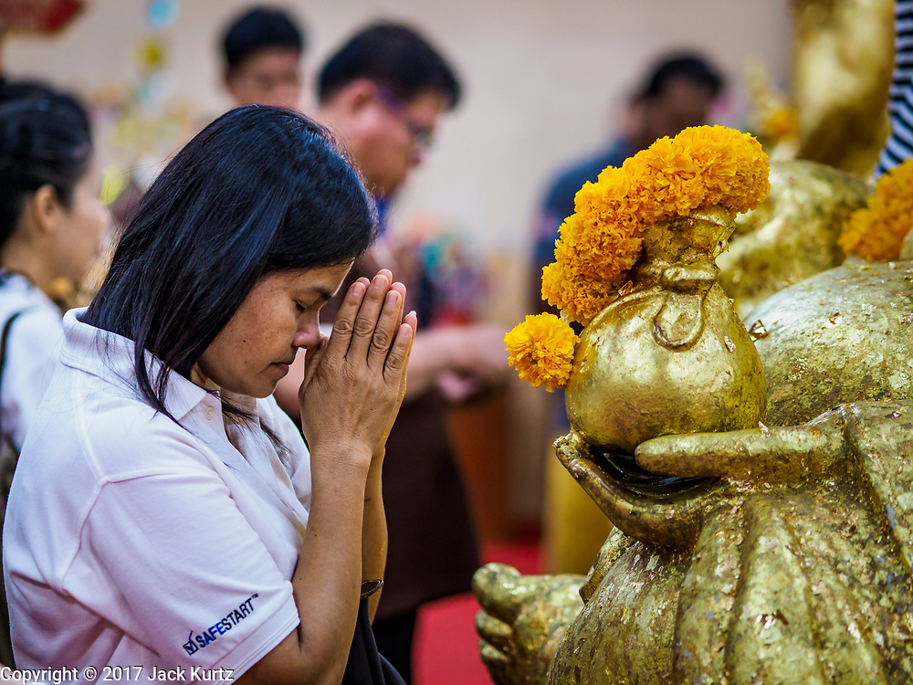 31 MAY 2017 - CHACHOENGSAO, THAILAND: A woman prays at Wat Sothon (also spelled Sothorn) in Chachoengsao, Thailand. The temple is one of the largest and most visited in Thailand. People make merit by paying to wrap the Buddha statues in orange robes. The temple is most famous because people leave hard boiled eggs as an offering at the temple. They ask for business success or children and leave hundreds of hard boiled eggs.      PHOTO BY JACK KURTZ