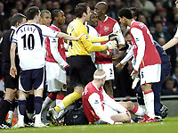 Photo: Olly Greenwood.<br />Arsenal v Tottenham Hotspur. Carling Cup Semi Final 2nd leg 31/01/2007. Arseenal and Spurs player tussle while Philippe Senderos receives treatment from a challenge by Hossam Ghaly
