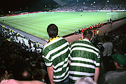 Two Celtic fans get out of their seat to watch the action on the pitch at Celtic's ground, Parkhead. Celtic have a strong following of mostly Irish Catholics and are bitter rivals to the city's other team, Glasgow Rangers.
