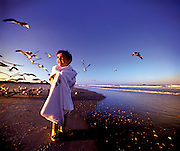 A boy walks down the beach wrapped in a towel with seagulls flying above him