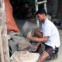 Asia, India, Calcutta. Man pounds clay in the potter's village of Kumartuli in Calcutta.