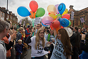 Teenage campaigners against the closure by Lambeth council  of Carnegie Library in Herne Hill, south London, charge through Brixton, after emerging from the premises on the 10th day of occupation, 9th April 2016. The local community have been occupying their important resource for learning and social hub and after a long campaign, Lambeth have gone ahead and closed the librarys doors for the last time because they say, cuts to their budget mean millions must be saved. They plan to re-purpose it into a gym although details are unknown.