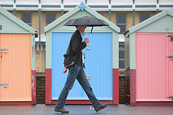 © under license to London News Pictures. 12/06/12. Heavy rainfall across the south east, a Man walks with a an umbrella on brighton seafront next to some brightly coloured beach huts. The met office has issued severe weather warnings in England and Wales. Unseasonal weather in the south east has caused flooding. Sussex has been badly hit. Brighton XAVIER ITTER/LNP