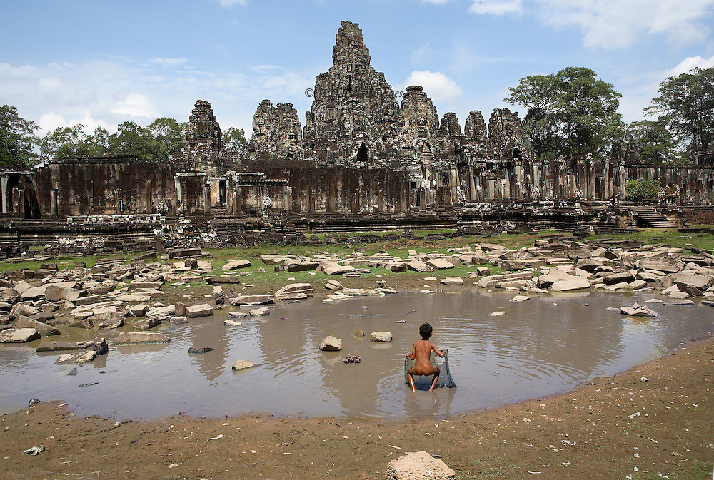 Angkor Thom: naked young boy about 6 years old fishing with aa ragged net in the rubble-filled remains of the moat outside the perimeter wall of Bayon, southwest side.  Rear view of the child lifting the net.