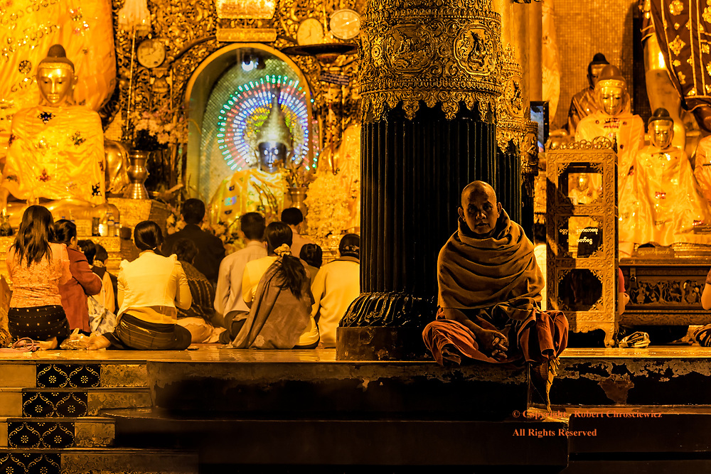 Contrarian View: A Buddhist monk sitting on the edge of a temple takes a contrarian stance and so, rather than looking inwards like the other devotes, his gaze is outwards, directed at the foreigner across the marquee, Shwedagon Pagoda, Yangon Myanmar.