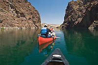 Reflections of the walls of The Black Canyon, Nevada fall onto paddlers navigating down the Colorado River.