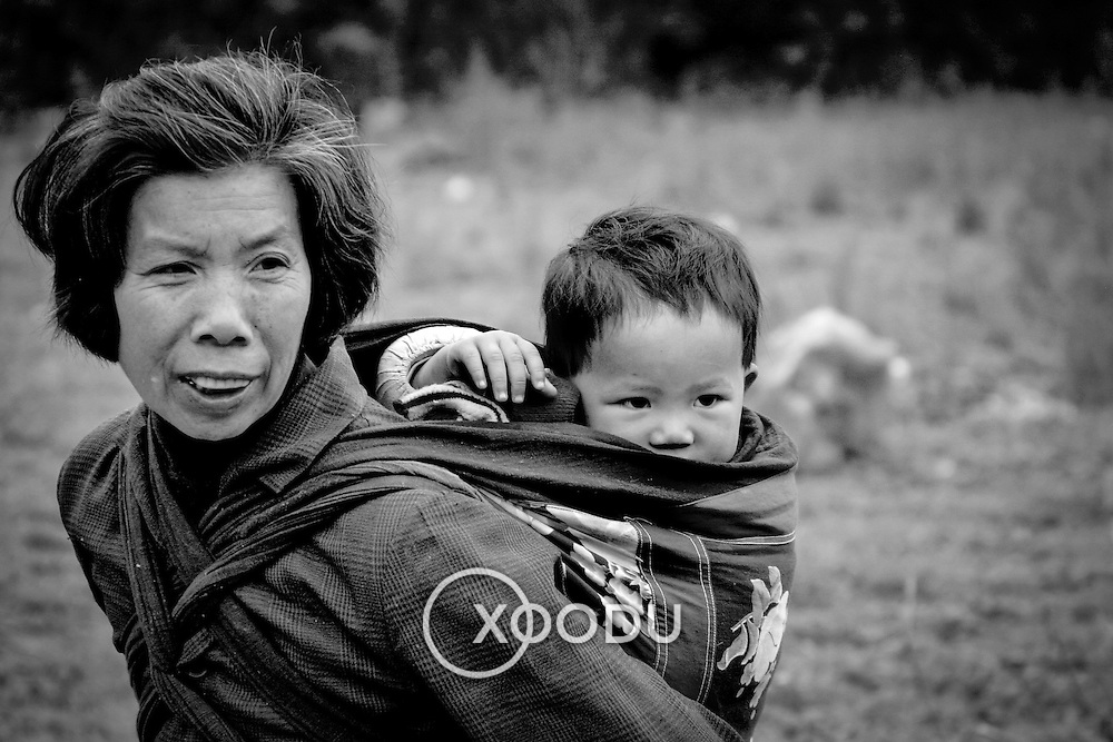 Woman with child on back, Yangshuo, China (May 2004)