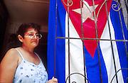 25 JULY 2002 - HAVANA, HAVANA, CUBA: A woman in her doorway with a Cuban flag in the historic section of Havana, Cuba, July 25, 2002..PHOTO BY JACK KURTZ