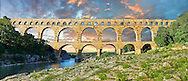 Picture of the ancient Roman Aqueduct of the Pont du Gard which crosses the River Gardon near Vers-Pon-du-Gard, France. Part of the 50 km long aqueduct that served the Roman town of Nemausus (Nimes) its 3 tiers of arches stand 48 m high (160 ft). A UNESCO World Heritage Site. .<br /> <br /> Visit our ROMAN ART & HISTORIC SITES PHOTO COLLECTIONS for more photos to download or buy as wall art prints https://funkystock.photoshelter.com/gallery-collection/The-Romans-Art-Artefacts-Antiquities-Historic-Sites-Pictures-Images/C0000r2uLJJo9_s0