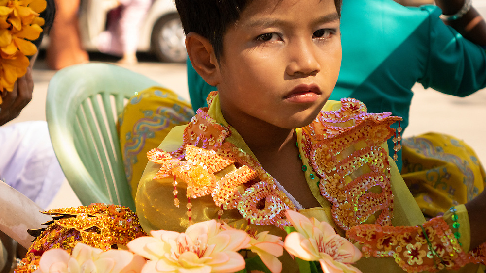 A young boy in traditional attire attends a parade during the Shinbyu novitiation ceremony. The Shinbyu novitiation ceremony is an essential and integral part in a life of a Myanmar Buddhist male under the age of 20