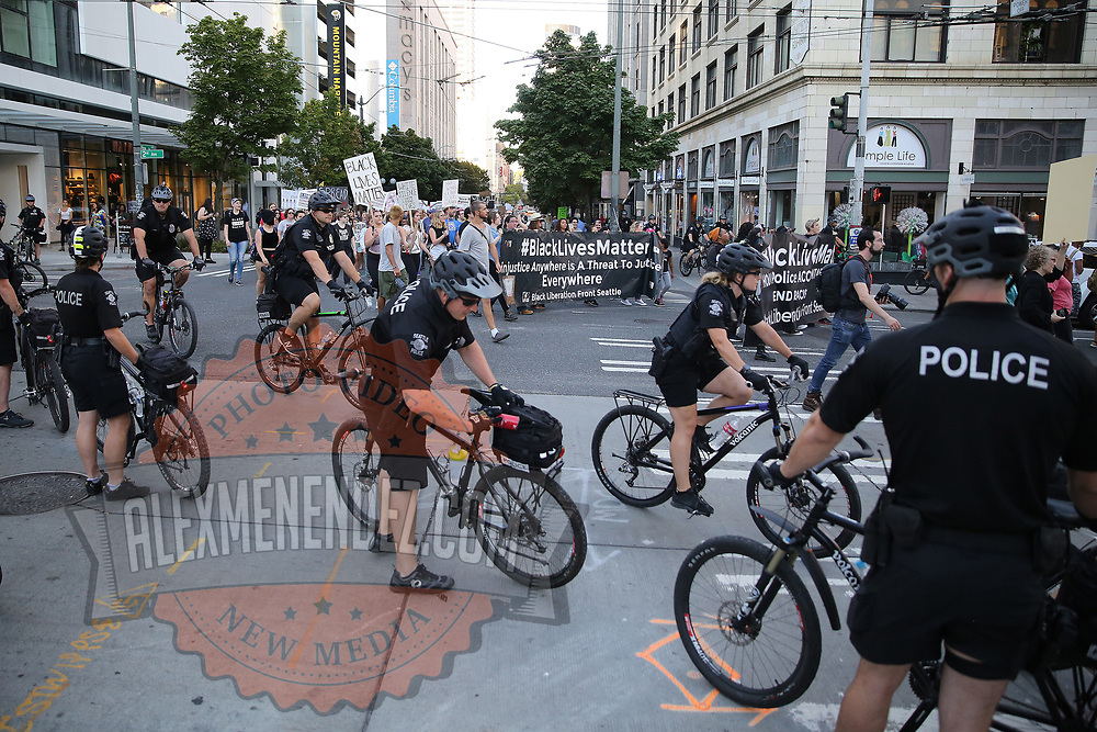 Seattle police officers are seen as protesters take part in a Black Lives Matter march, Saturday, August 26, 2017, in Seattle, Washington. Several thousand people attended a downtown rally and then marched through the city to call attention to minority rights and police brutality. (Alex Menendez via AP)