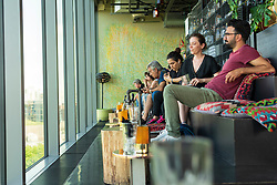 View of customers in the rooftop Monkey Bar at fashionable 25hours Hotel in Berlin, Germany