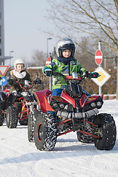 Children riding quad bike on snow