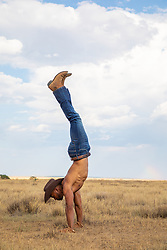 shirtless muscular cowboy doing a handstand on a rustic ranch