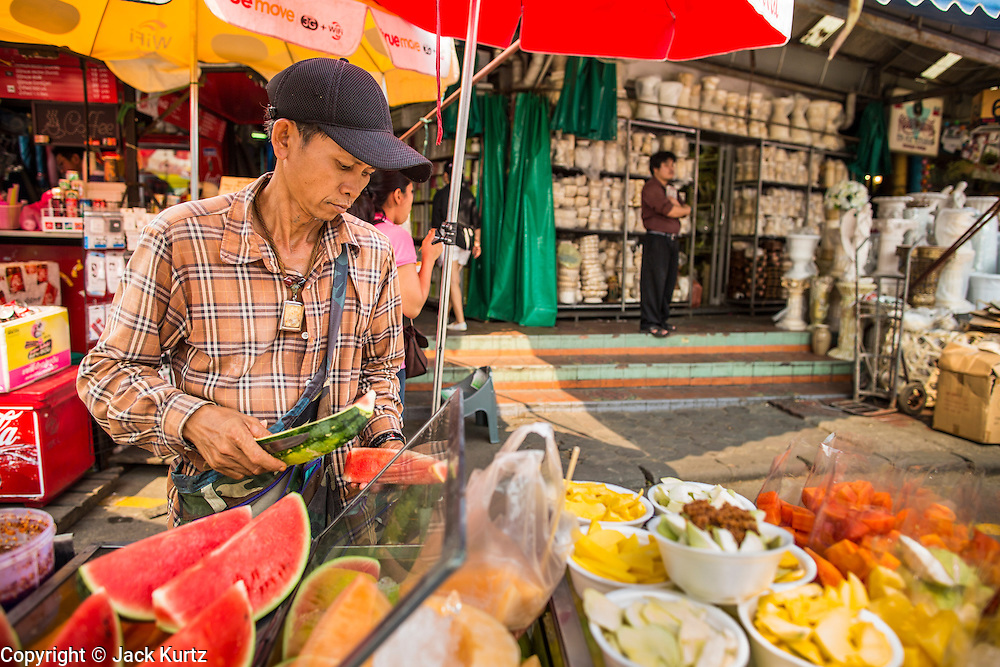 16 FEBRUARY 2013 - BANGKOK, THAILAND:       A fruit vendor in Chatuchak Weekend Market in Bangkok. It is reportedly the largest market in Thailand and the world's largest weekend market. Frequently called J.J., it covers more than 35 acres and contains upwards of 5,000 stalls.        PHOTO BY JACK KURTZ