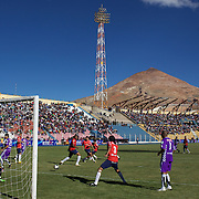 'Attitude at Altitude' Football in Potosi, Bolivia'..Action during the match between Real Potosi and Wilstermann at the The Estadio Victor Agustin Ugarte, Potosi, Bolivia, with the infamous Cerro Rico mountain providing the backdrop. Real Potosi won the match 3-0. 2nd May 2010. Photo Tim Clayton..'Attitude at Altitude' Football in Potosi, Bolivia'..The Calvario players greet the final whistle with joyous celebration, high fives and bear hugs the players are sprayed with local Potosina beer after a monumental 3-1 victory over arch rivals Galpes S.C. in the Liga Deportiva San Cristobal. The Cup Final, high in the hills over Potosi. Bolivia, is a scene familiar to many small local football leagues around the world, only this time the game isn't played on grass but a rock hard earth pitch amongst gravel and boulders and white lines that are as straight as a witches nose, The hard surface resembles the earth from Cerro Rico the huge mountain that overlooks the town. .. Sitting at 4,090M (13,420 Feet) above sea level the small mining community of Potosi, Bolivia is one of the highest cities in the world by elevation and sits 'sky high' in the hills of the land locked nation. ..Overlooking the city is the infamous mountain, Cerro Rico (rich mountain), a mountain conceived to be made of silver ore. It was the major supplier of silver for the spanish empire and has been mined since 1546, according to records 45,000 tons of pure silver were mined from Cerro Rico between 1556 and 1783, 9000 tons of which went to the Spanish Monarchy. The mountain produced fabulous wealth and became one of the largest and wealthiest cities in Latin America. The Extraordinary riches of Potosi were featured in Maguel de Cervantes famous novel 'Don Quixote'. One theory holds that the mint mark of Potosi, the letters PTSI superimposed on one another is the origin of the dollar sign...Today mainly zinc, lead, tin and small quantities of silver are extracted from the mine by over 100 co operatives an